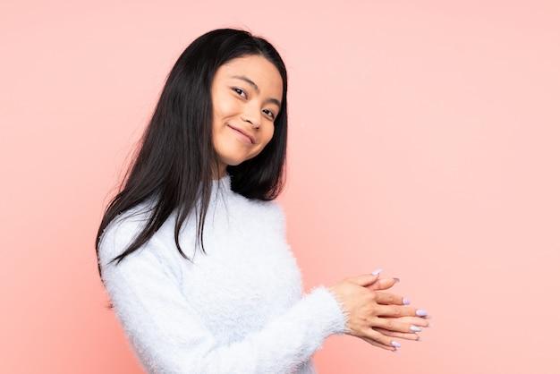 Tiener chinese vrouw die bij het roze muur toejuichen wordt geïsoleerd