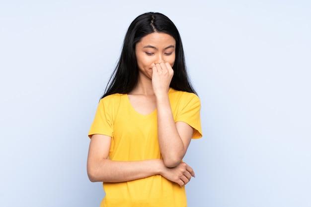 Tiener chinese vrouw die op blauwe muur wordt geïsoleerd die twijfels heeft