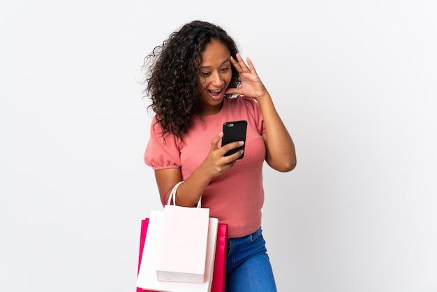 Tiener cubaans meisje geïsoleerd op wit bedrijf boodschappentassen en het schrijven van een bericht met haar mobiele telefoon naar een vriend