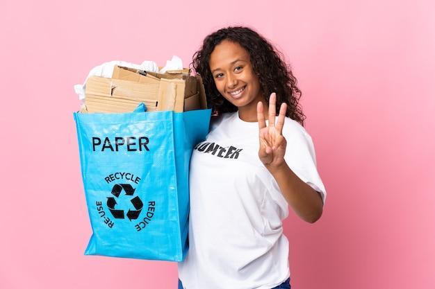 Tiener cubaans meisje met een recycling zak vol papier om te recyclen geïsoleerd op roze muur gelukkig en drie tellen met vingers