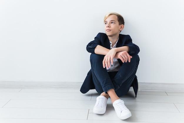 Tiener depressie en puberteit concept - triest tiener portret close-up op witte muur.