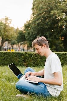 Tiener die aan laptop in het park werkt