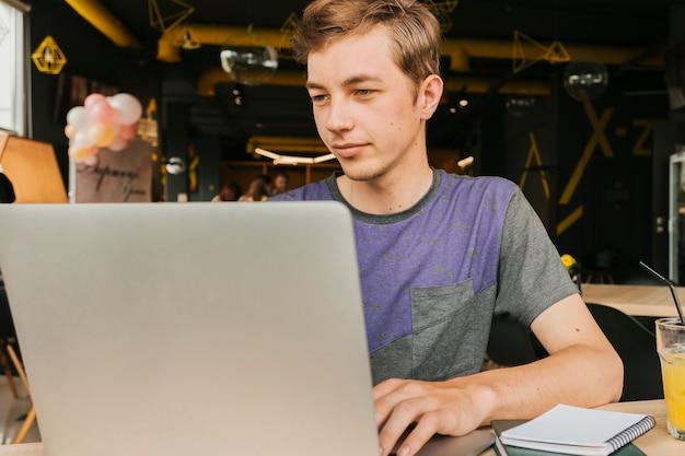 Tiener die aan laptop werkt