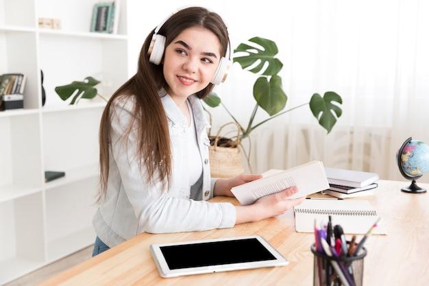 Tiener die aan muziek luistert terwijl het bestuderen
