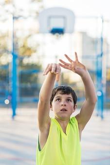 Tiener die basketbal speelt op een buitenbaan
