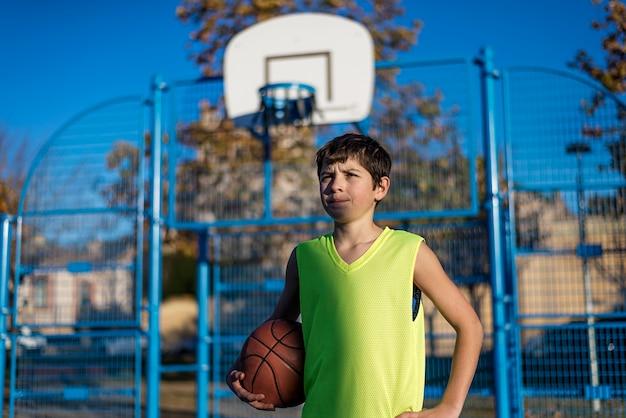 Tiener die een basketbal op een baan houdt