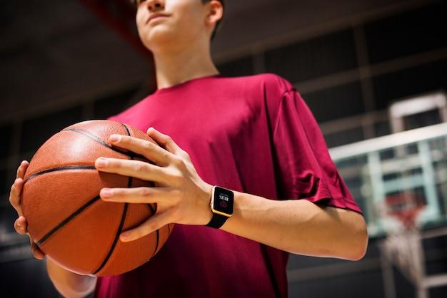 Tiener die een basketbal op het hof houdt
