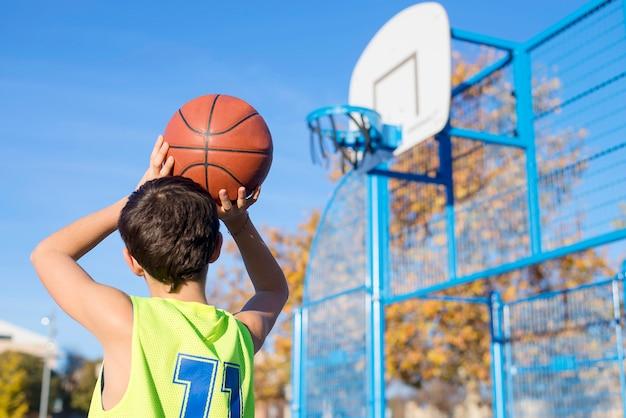 Tiener die een basketbal van achteren in de hoepel gooit