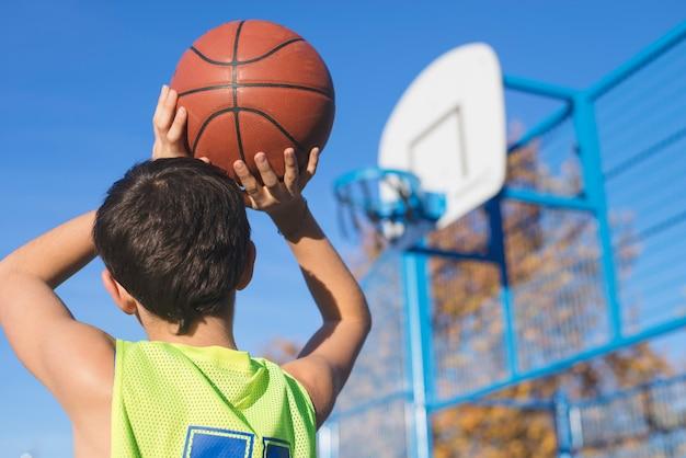 Tiener die een basketbal werpt in de hoepel