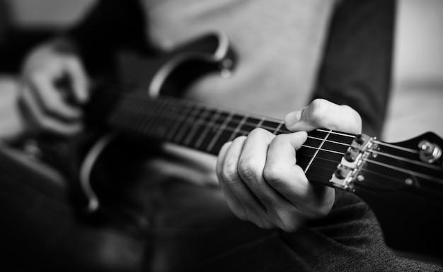 Tiener die een elektrische gitaar in een een slaapkamerhobby en muziekconcept speelt