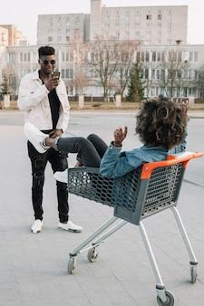 Tiener die een foto van vriend in boodschappenwagentje neemt