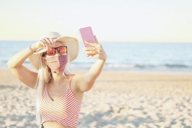 Tiener die een selfie neemt bij het strand met gezichtsmasker op
