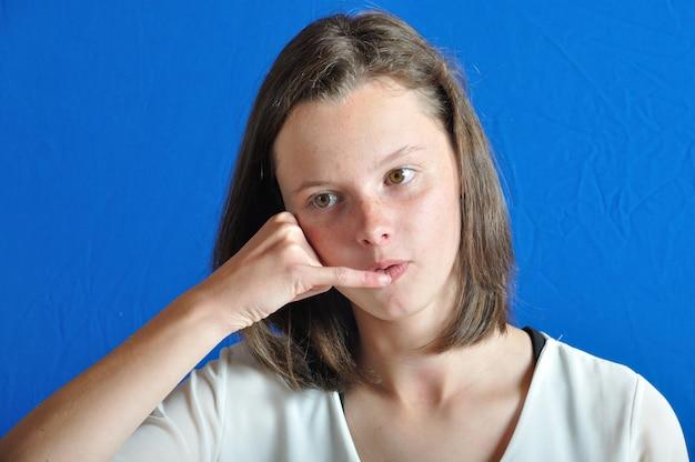 Tiener die een telefoon met haar hand nabootst