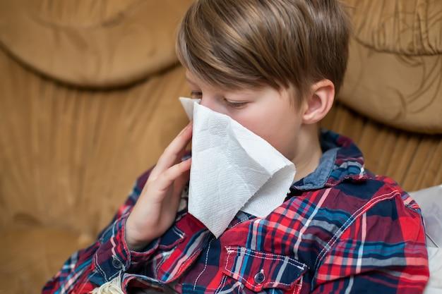 Tiener die haar lopende neus in papieren zakdoekjeszakdoek thuis blazen. chronische loopneus bij het kind. symptoom van covid-19 respiratoir virus.