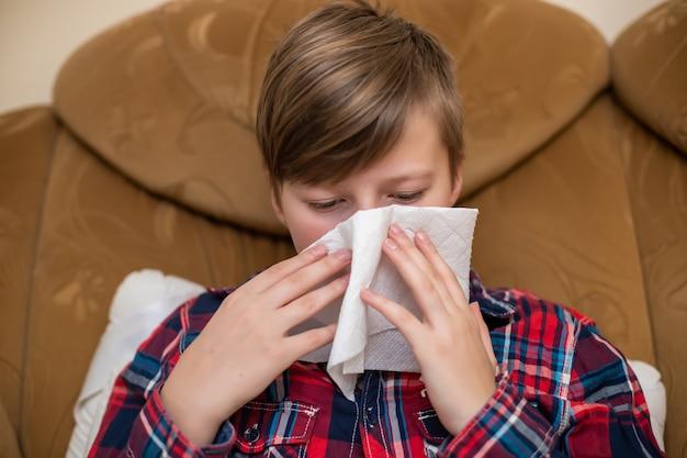 Tiener die haar lopende neus in papieren zakdoekjeszakdoek thuis blazen. chronische loopneus bij het kind.