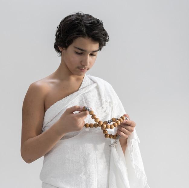 Tiener die ihram voor hadj met rozentuin draagt