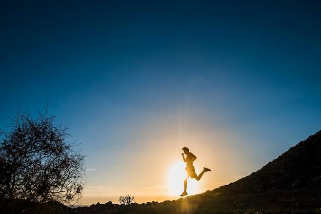 Tiener die in de bergen loopt bij de zonsondergang - hardlopersleven en sportief concept - buitenlevensstijl - boom en blauwe achtergrond