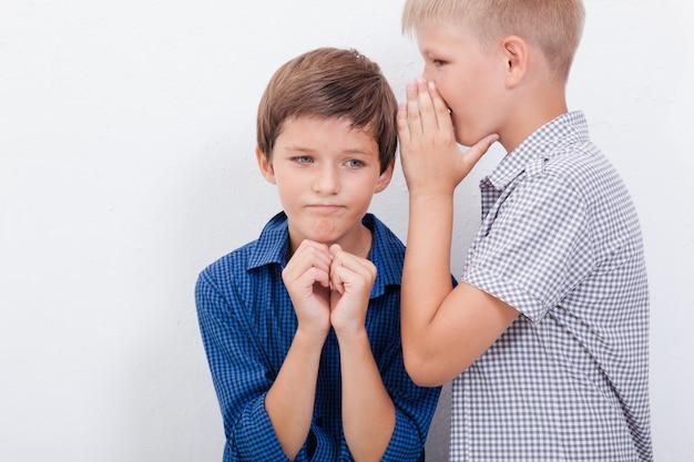 Tiener die in het oor een geheim fluistert aan vriend op witte muur