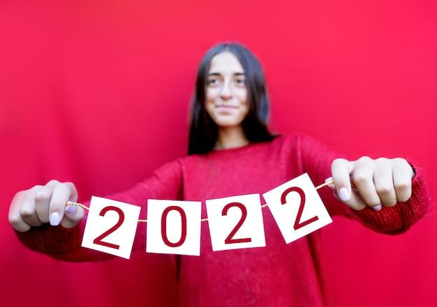 Tiener die kaarten van 2022 houdt. nieuwjaarsviering. jong meisje en kerststemming