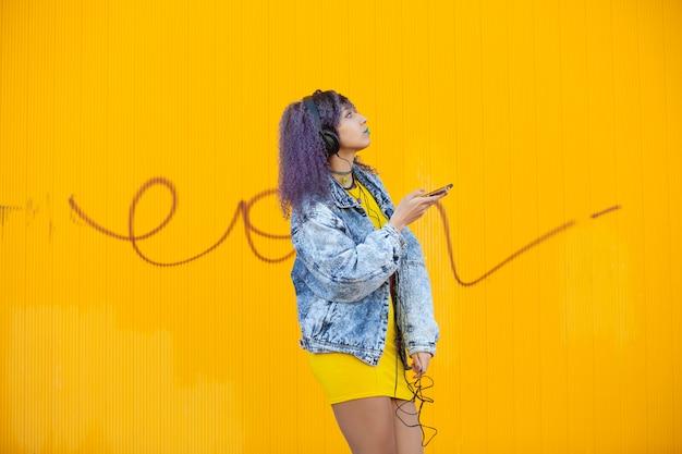 Tiener die met afrohaar aan muziek op een gele muur luistert