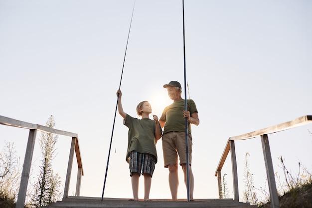 Tiener die met hengel leert vissen, opa die zijn kleinzoon onderwijst om vissen te vangen, volledig lengteportret op houten ponton met treden, mooie zonsondergang.