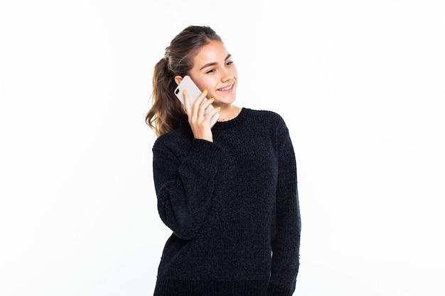 Tiener die op een celtelefoon spreekt die op witte muur wordt geïsoleerd