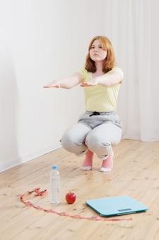 Tiener die sporten thuis, elektronische schalen op de vloer doet
