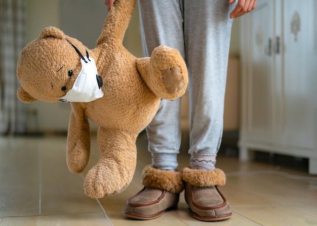 Tiener die teddybeer met gezichtsmasker koestert.
