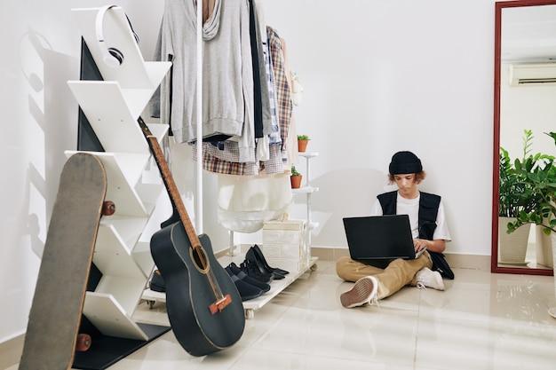 Tiener die thuis blijft wegens pandemie van het coronavirus en aan laptop werkt