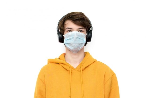 Tiener die thuis in een medisch masker en met een rugzak tijdens coronovirus wordt geïsoleerd.