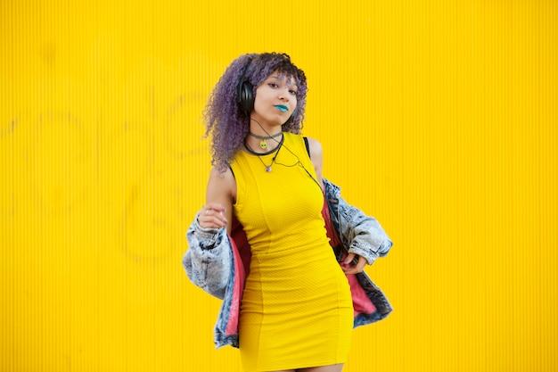 Tiener die tussen verschillende rassen aan muziek met grote hoofdtelefoons op een gele muur luistert