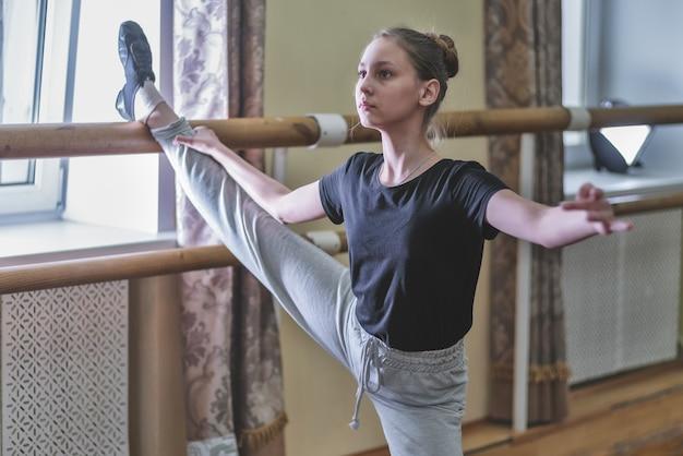 Tiener doet oefeningen in de dansles op de bank