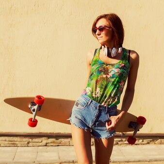 Tiener draagt een zonnebril en een koptelefoon op een zomerse dag