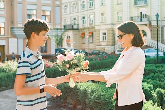 Tiener feliciteer moeder met boeket bloemen