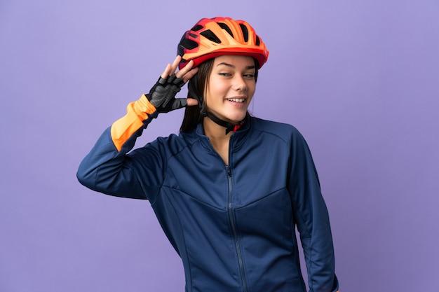 Tiener fietser meisje luistert naar iets door hand op het oor te leggen