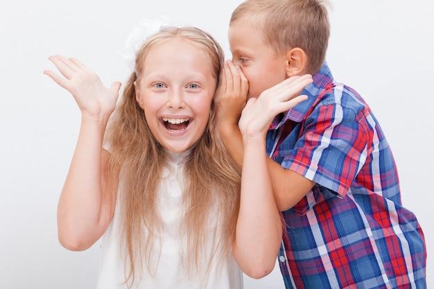 Tiener fluistert in het oor een geheim voor tienermeisje