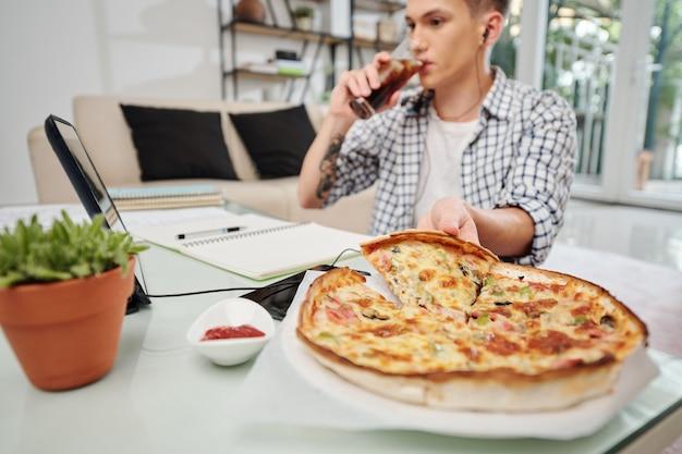 Tiener frisdrank drinken en pizza eten bij het voorbereiden van examens thuis