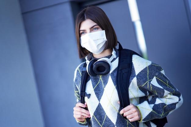 Tiener gaat naar school met een masker op vanwege de pandemie van het coronavirus