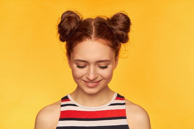 Tiener, gelukkig ogende, charmante roodharige vrouw met twee broodjes. gestreept overhemd dragen en met een glimlach naar beneden kijken, verlegen. close-up, tribune geïsoleerd over gele muur