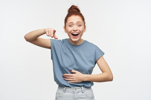 Tiener, gelukkig ogende vrouw met gemberhaar verzameld in een knot. blauw t-shirt en spijkerbroek dragen. lachend en haar buik aanraken. geïsoleerd over witte muur