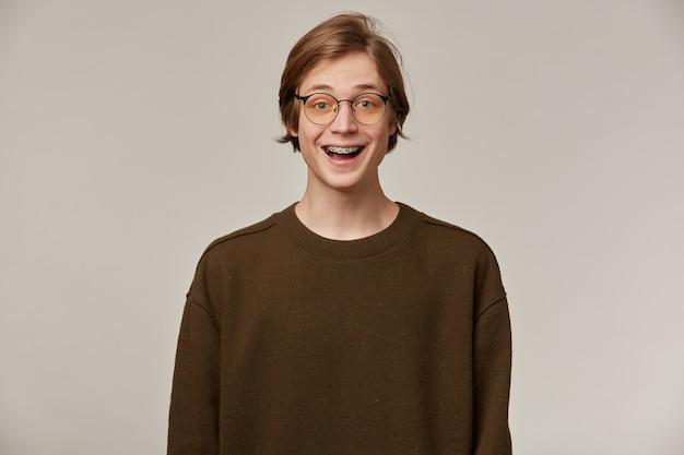 Tiener, gelukkig uitziende man met blond haar. bruine trui en bril dragen. heeft beugels.