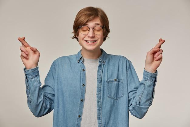 Tiener, gelukkig uitziende man met blond haar. hij draagt een blauw spijkerblouse, een bril en heeft bretels. kruis zijn vingers en houdt de ogen gesloten. een wens doen. stand geïsoleerd over grijze muur