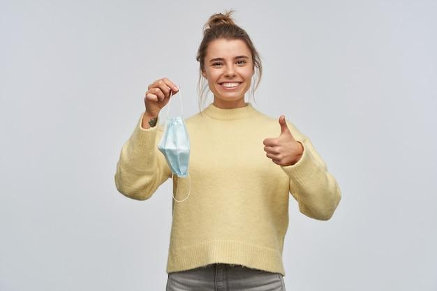 Tiener, gelukkig uitziende vrouw met blond haar verzameld in een broodje. gele trui dragen. beschermend gezichtsmasker vasthouden en duim opdagen. kijkend naar de camera, geïsoleerd over witte muur