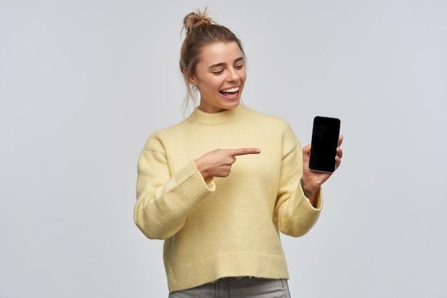 Tiener, gelukkig uitziende vrouw met blond haar verzameld in een broodje. gele trui dragen. kijken en wijst naar het telefoonscherm, kopieer ruimte. tribune geïsoleerd over witte muur