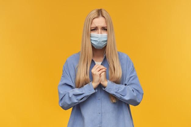 Tiener, gelukkig uitziende vrouw met blond lang haar. het dragen van een blauw shirt en een medisch gezichtsmasker, biddend. mensen en emotie concept. kijken, geïsoleerd op oranje achtergrond