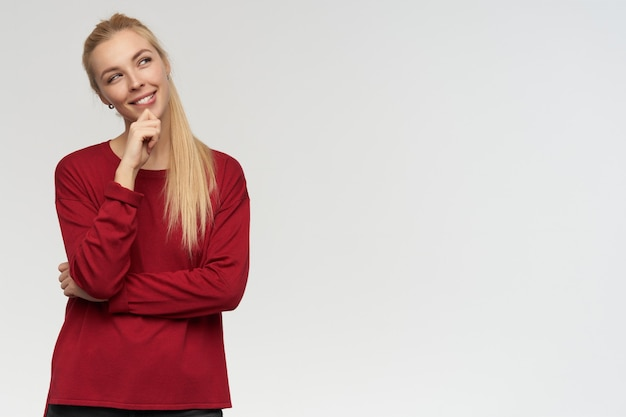 Tiener, gelukkig uitziende vrouw met blond lang haar. rode trui dragen. mensen en emotie concept. kijken zorgvuldig naar rechts op kopie ruimte, geïsoleerd op witte achtergrond