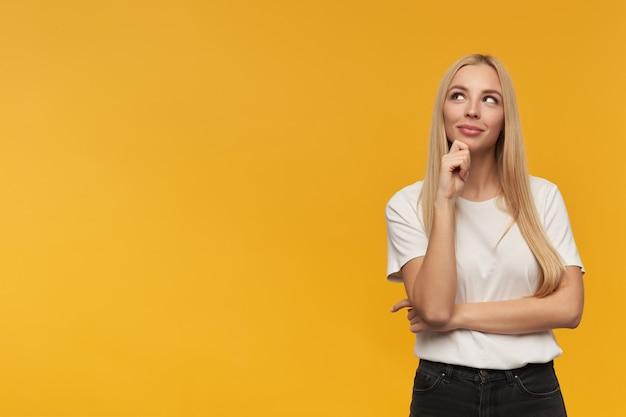 Tiener, gelukkig uitziende vrouw met blond lang haar. witte t-shirt en zwarte spijkerbroek dragen. mensen en emotie concept. kijken naar links op kopie ruimte, geïsoleerd op oranje achtergrond