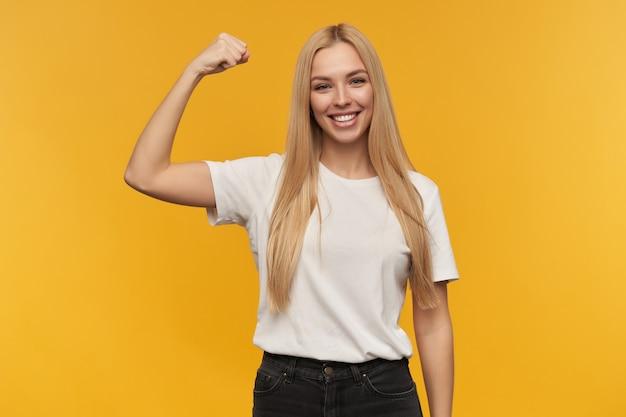 Tiener, gelukkig uitziende vrouw met blond lang haar. witte t-shirt en zwarte spijkerbroek dragen. toont haar spieren kijken naar de camera, geïsoleerd op oranje achtergrond