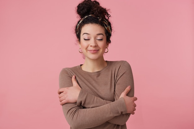 Tiener, gelukkig uitziende vrouw met donker krullend haarbroodje. met hoofdband, oorbellen en bruine trui. heeft make-up. houdt de ogen gesloten en knuffelt zichzelf