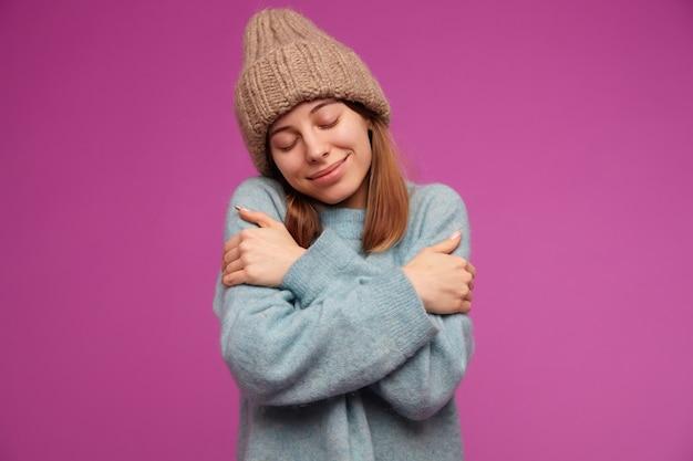 Tiener, gelukkig uitziende vrouw met donkerbruin lang haar. het dragen van blauwe trui en gebreide muts. knuffel haar zelf, voelt warm en gezellig boven de paarse muur